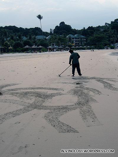 Resort staff raking the sand
