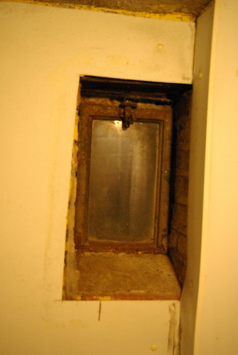 The tinest basement window, under the front stoop