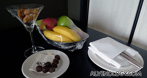 Dining table whereby a platter of fruits, chocolate and cookies welcome us