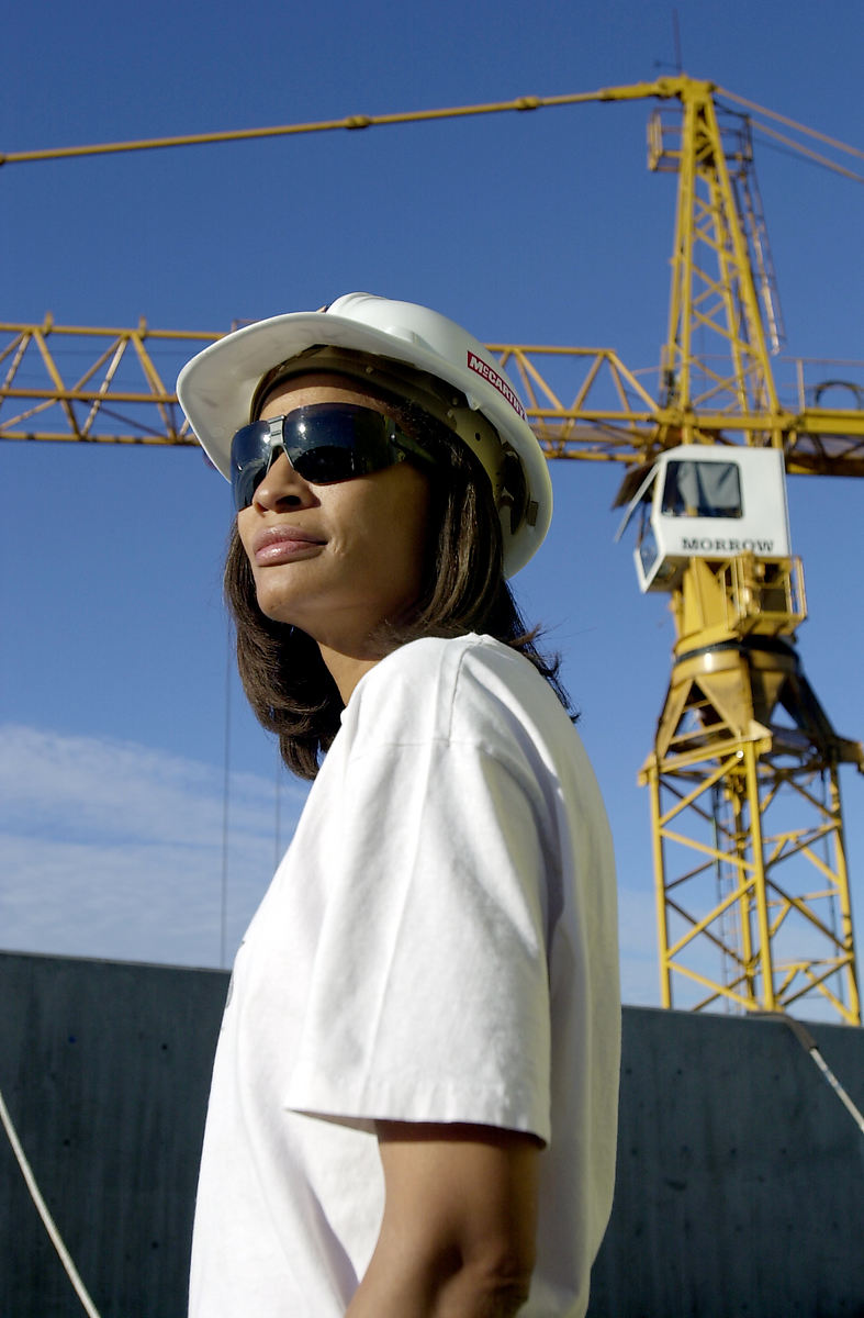 woman at construction site wearing a white tshirt, sunglasses, and hard hat