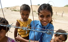 Curiosity (Daniel Bachhuber) Tags: travel summer portrait people india smiling kids town holding afternoon village looking desert group sunny barbedwire rajasthan gravis naturallighting thardesert india08