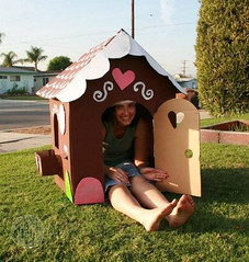 Life size gingerbread house painted and decorated with a woman sitting inside