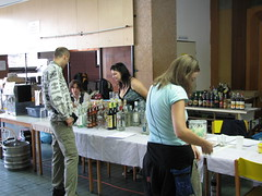 Two people browsing a table that has dozens of assorted liquor bottles on it
