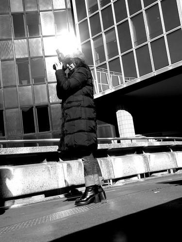 Photographe au pied des tours de l'esplanade de la Défense (Paris)