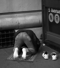 5th Avenue Prayer (StaceyDePhoto) Tags: nyc urban blackandwhite usa newyork man streets subway shoes pavement manhattan muslim prayer religion 5thavenue streetscenes theaterdistrict kneelingman prayerrug