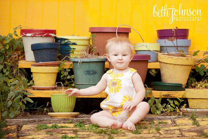 baby girl in front of colorful pots at railroad square
