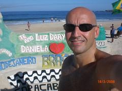 eu em primeiro plano com a praia de Copacabana ao fundo e a mensagem para esposa e filha na areia