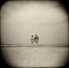 Couple at Beach (James Godman) Tags: ocean ladies sea two people blackandwhite woman lake seascape man male men love beach water senior loving lady female standing outside outdoors person togetherness stand back holga sand women couple quiet married adult horizon union marriage peaceful tranquility wave husband spouse overcast collection elderly shore wife serene holdinghands rearview distance retired seashore oldage tranquil seniors retirement grandparent distant seniorcitizens seniorcitizen jamesgodman