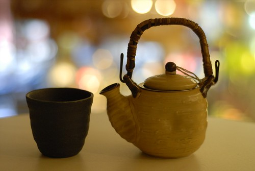 A handle-less unglazed black ceramic teacup sits next to a glazed white teapot with a raffia-wrapped handle.