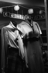 come on in (gguillaumee) Tags: street nyc light people bw newyork film mannequin glass shop brooklyn night dark mood shadows candid delta clothes invitation thrift williamsburg 50s illford oldie oldfashioned nikonf80 comeonin 3200iso
