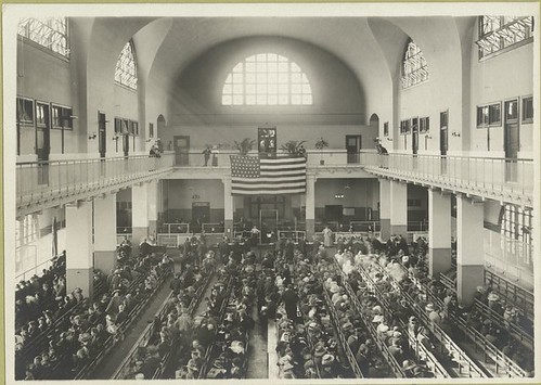 Immigrants seated on long benches, Main Hall, U.S. Immigrati...