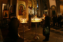 Old woman lights a candle in Kazanski Cathedral