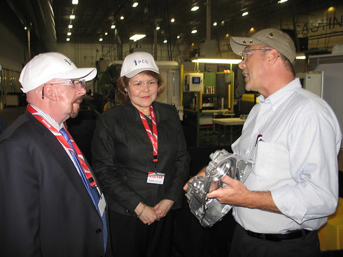 Vice President of Operations Scott Maus (right) displays a completed component produced at the Port City Group's East Port Road facility to USDA Rural Development State Director for Michigan James J. Turner and Rural Business Administrator Judith Canales.