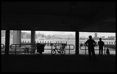 Frame-Kwun Tong, Kowloon (Paul Swee) Tags: blackandwhite bike bicycle silhouette composition hongkong streetphotography monotone 20mm ilfordxp2 kowloon underthebridge  victoriaharbour f6 paulswee leicammount  2006aprroll3