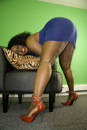 A big fat ebony beauty poses in a yoga-like pose