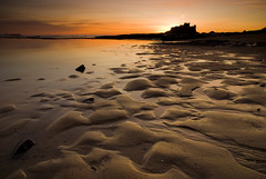 Bamburgh Castle | Sunrise (Paul Santos Photography) Tags: england orange seascape cold castle texture water silhouette contrast sunrise sand warm ripple tide samsung explore northumberland 1750 rippled tamron bamburgh gx10 explored