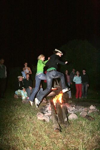Zwei Frauen springen über ein Lagerfeuer