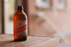 Red Stripe at P.S.1 (Inside_man) Tags: summer stilllife newyork cafe colorful artgallery drink bokeh brickwall woodtable jamaicanlager sooc ps1contemporaryartcenter redstripeatps1