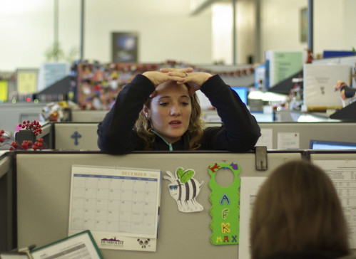 woman leaning over cubicle and talking to a coworker