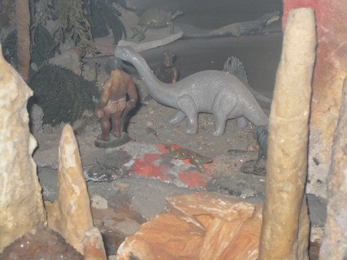 A caveman hanging out with a dinosaur
