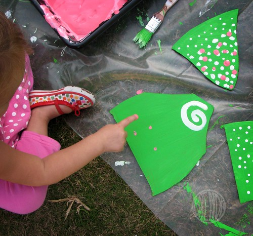 child adding paint sprinkles to cardboard pieces