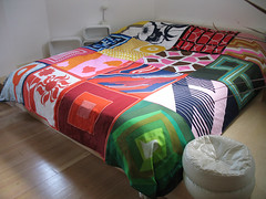 Vintage scarf quilt, on bed platform in the old altar (ouno design) Tags: geometric scarf vintage design mod 60s quilt recycled silk khaki thrift 70s chic scarves textiles technicolor sustainable hemp acetate remnant salvaged reversible upcycled craftmagazine robotflowers vintagescarfquilt