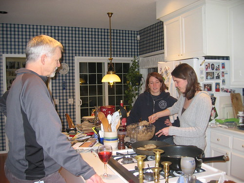 Rebecca cooking latkes; Fitz and Jessica supervising