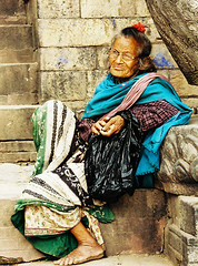 Blue Shawl - explored (nida shams) Tags: camera old travel blue nepal red woman flower heritage film nikon asia culture grace aged shawl 2008 spectacles sari nida shams bakthapur kathmundu