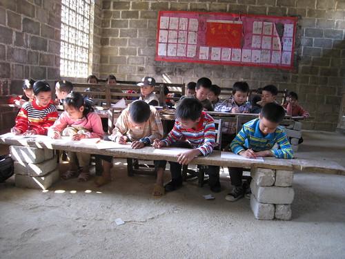在用砖头垒起的桌子上,孩子们在画画