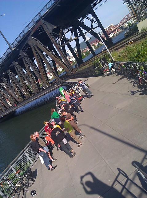 Photo of a gathering of cyclists at the foot of the Steel Bridge in Portland, with the shadow of photographer DarkEmeralds prominent in the foreground
