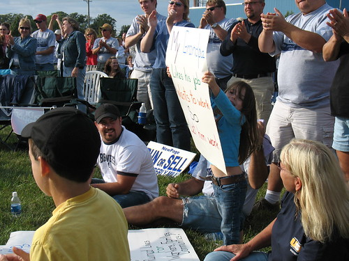 A group of people holding up signs during a rally.