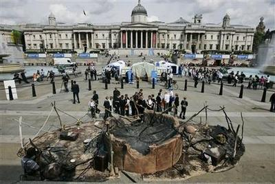 School pupils look at a representation of a Darfur village supposedly destroyed during the war, in central London's Trafalgar Square, build by UNHCR as part of global commemorations of World Refugee Day later this week