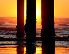 Peering Through (Yobs) Tags: sunset reflection beach silhouette pier