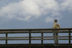 A woman in a yellow jacket stands on a wooden bridge looking into a blue sky slightly obscured by clouds.