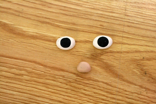 Made the eyes and cute button nose from Sculpey. You cant see it, but theres a hole running horizontally through each eye, and vertically through the nose so I could sew them on later.