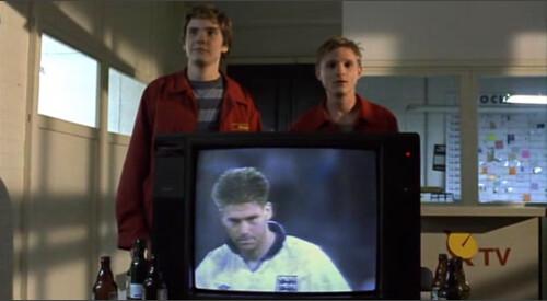 Fotograma de Good Bye Lenin de los dos chicos detrás del televisor mientras sus compañeros de trabajo ven la final a penaltis de un partido de fútbol del mundial del 90