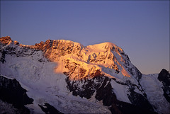 breithorn sunrise (Ron Layters) Tags: pink red orange mountain snow yellow sunrise geotagged dawn switzerland purple pentax earlymorning slide glacier velvia transparency zermatt kleinmatterhorn northface fujichrome wallis alpenglow valais seracs pentaxmz10 breithorn mountainsalps elevation40004500m summitbreithorn summitridge mattertal ronlayters 4165m slidefilmthenscanned altitude4165m therearefivesummitsontheridge geo:lat=45942436 geo:lon=7736263