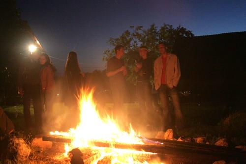 Menschen stehen am Lagerfeuer