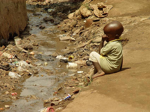 Child in slum in Kampala (Uganda) next to open sewage