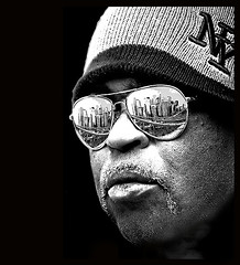 that's a nyc face . . . (daystar297) Tags: nyc bw newyork black face hat sunglasses skyline photoshop reflections availablelight manhattan streetportrait manipulation brooklynbridge africanamerican veteran lowermanhattan streetvendor onblack damniwishidtakenthat