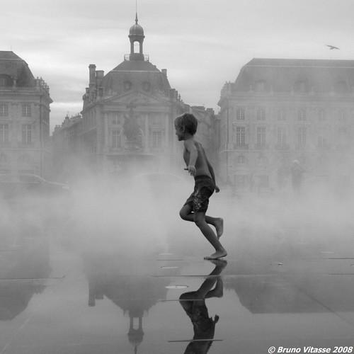 Enfant courant dans la brume du miroir d'eau (Bordeaux)