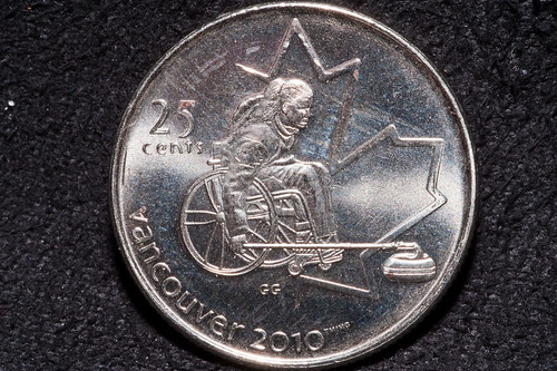 A Canadian quarter (25 cents) showing a woman using a wheelchair for curling