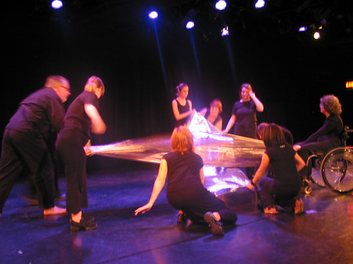 dancers holding shiny sheets of fabric