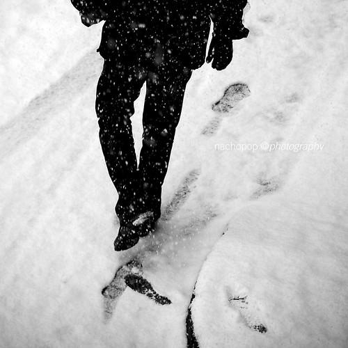 Fotografía de un hombre vestido de oscuro que camina de espaldas dejando sus huellas sobre el suelo en un día de nieve