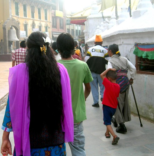 Tibetans praying at the Boudha Stupa, one man wearing a 'China' shirt, Kathmandu, Nepal