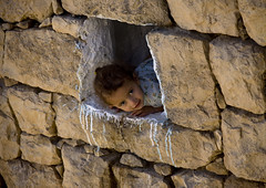 Young girl showing up at the window - Yemen (Eric Lafforgue) Tags: wall stones explore arabia yemen arabian ramadan yemeni 6199 lafforgue arabiafelix  arabieheureuse