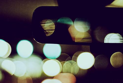 Fotografía tomada desde el interior de un coche, se ve el espejo retrovisor interior y un montón de luces al fondo haciendo efectos de bokeh circulares