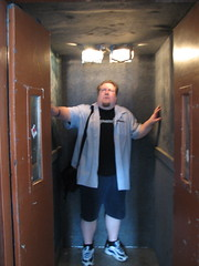 Jukka standing in a shabby elevator, with walls covered in carpeting, bright lights, and ominous metal doors