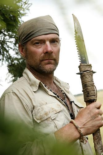 Surviorman Les Stroud holding a knife