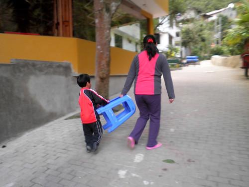 niño ayuda a llevar sillas sin necesidad